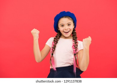 Fashion girl. Fashionable beret accessory. Teenage fashion. French fashion attribute. Child small girl happy smiling baby. Kid little cute fashion girl posing with long braids and hat red background.