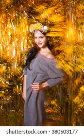 fashion girl in a gray sweater on a gold background