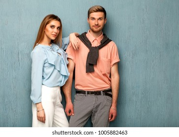 Fashion girl and guy in outlet clothes posing on a blue background. Valentines Day.