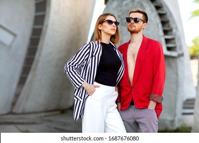 Fashion girl and guy in outlet clothes posing on a white background