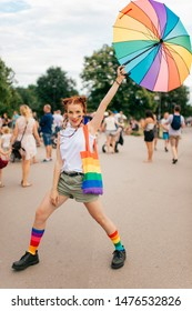 fashion girl with lgbt gay pride flag on her face, colorful umbrella, bag and mismatched socks posing on street with people on background.