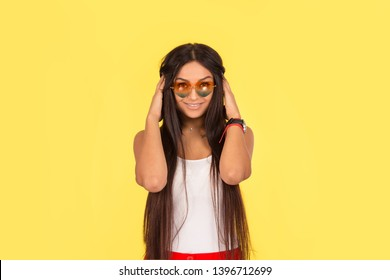 Fashion girl looks at camera. Fashionable young woman touching adjusting her long black hair extensions isolated on yellow background.  Multicultural ethnic model, mixed race Indian African American.