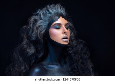 Fashion girl with lots of curls, long curly hair. Stylish brunette with painted face, sugar lips, bright color makeup. Portrait of woman on black background