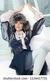 Fashion girl model posing in fur furry hat. Beautiful Woman in Luxury clothes in white interior