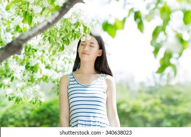 fashion girl outdoor portrait, young woman walking in summer park and with long black hair, toned and noise added
