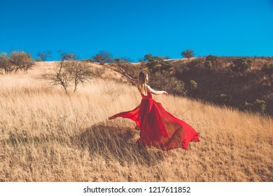 Fashion girl in a red dress in fields Nogales, Sonora, Mexico