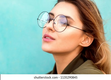 fashion girl in round glasses stands posing near a turquoise wall