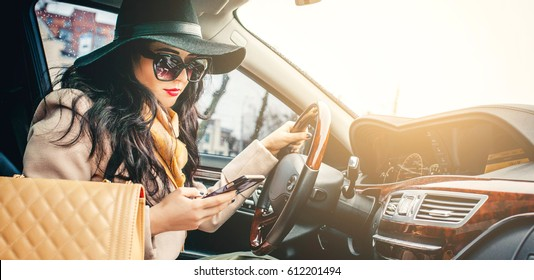 Fashion girl sits behind the wheel of a premium car and looks the way in her phone