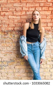 fashion girl standing near brick wall in denim and sneakers. Vogue Style
