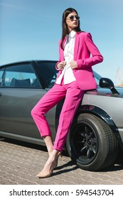 Fashion girl standing next to a retro sport car. Stylish woman in a pink suit waiting near classic car. Mafia lady outside japonese car.