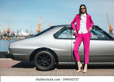 Fashion girl standing next to a retro sport car on the sun. Stylish woman in a pink suit waiting near classic car. Mafia lady outside japonese car in the sea port.