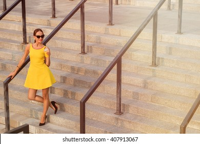 Fashion girl in sunglases posing with orange cocktail on stairs of building. Lady in yellow dress wearing black high heels. Toned image.