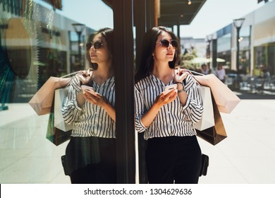 Fashion girl in sunglasses standing outdoor holding cellphone searching right direction cloth shop online map app on internet. young asian lady carrying shopping bag in shopping mall center