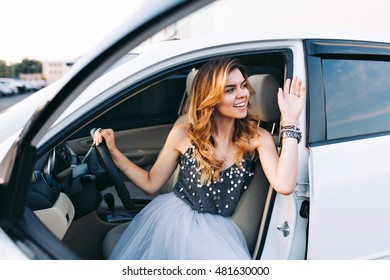 Fashion girl in tulle skirt driving white car. She gratulating somebody to side