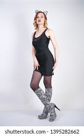 Fashion girl wearing black little dress from spandex with zebra velvet boots with high heels on white studio background