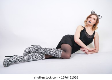 Fashion girl wearing black little dress from spandex with zebra velvet boots with high heels on white studio background alone
