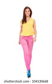 Fashion girl wearing yellow blouse and pink jeans walking towards the camera on white background