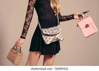 Fashion girl. Young woman posing in black dress and three hand bag.