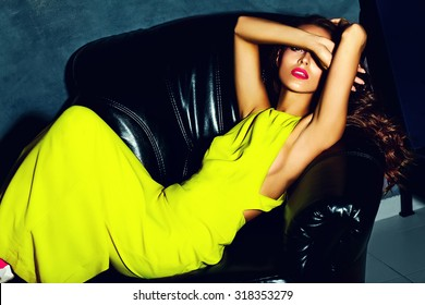 fashion glamor stylish beautiful  young woman model with red lips in summer bright colorful   yellow dress sitting on black sofa