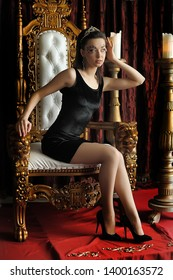 Fashion and glamour concept - sexy woman in crown and black dress sitting in throne.