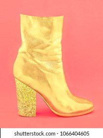 Fashion glamour one shiny golden women's shoe with heel made of confetti on pastel paper background. Trendy minimal pop art style and colors.