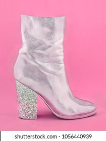 Fashion glamour one shiny silver women's shoe with heel made of confetti on pink paper background. Trendy minimal pop art style in pastel colored.