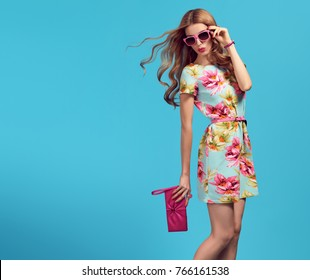 Fashion. Glamour Sexy Blond Model having fun. Young graceful woman in Floral Dress. Trendy, Stylish wavy Hairstyle, fashionable Sunglasses, Pink Clutch. Adorable Summer funny Girl, make up