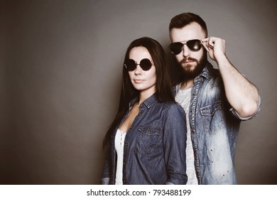 Fashion glasses concept. A young stylish fashion couple in casual clothes with black glasses look at the camera on a gray background.