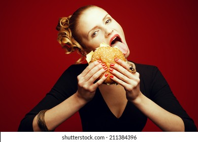 Fashion & Gluttony Concept. Happy red-haired model in black cocktail dress sticking out tongue & eating burger over red background. Perfect skin, make-up & manicure. Golden accessories. Studio shot