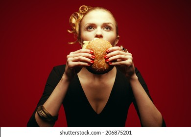 Fashion & Gluttony Concept. Portrait of luxurious red-haired model in black cocktail dress eating burger over red background. Funny curls, perfect skin, manicure. Golden accessories. Studio shot