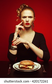 Fashion & Gluttony Concept. Portrait of luxurious red-haired model in black cocktail dress eating burger over red background. Perfect hair, skin, make-up, manicure. Golden accessories. Funny pigtail
