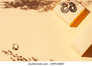 Fashion golden jewelry frame on the beige minimalistic background with harsh light. Top view. Copy space