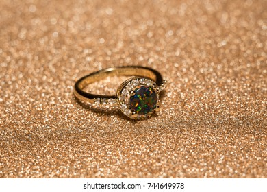 Fashion golden ring with synthetic fire opal stone of green color.