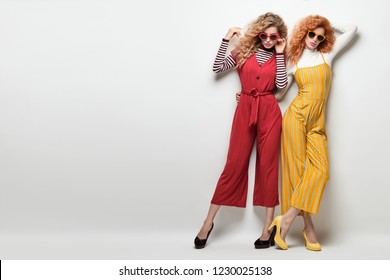 Fashion. Gorgeous Woman in Red Yellow jumpsuit, heels. Creative Elegant Style. Two Sexy Girl in Trendy Outfit with Curly Hairstyle. Young Playful Sisters Friends. Creative Vintage