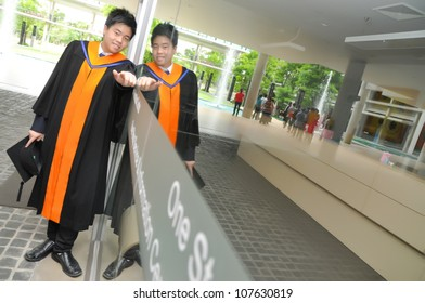 Fashion of graduate in thailand ,graduation boy holding his master's degree.And business action.