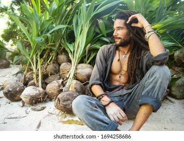fashion guy with dreadlocks in tropical coconut palms smiling