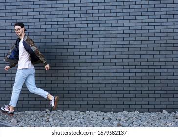fashion guy runs and poses brick black urban background
