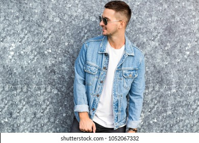 fashion guy standing by a blue marble wall posing in sunglasses