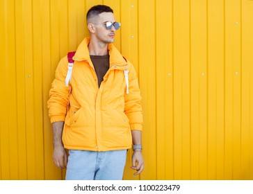 fashion guy standing near a yellow wall in yellow clothes