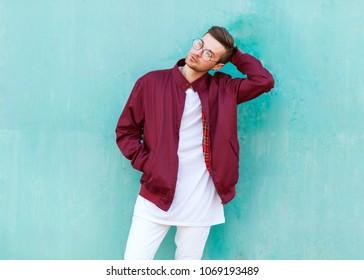 fashion guy standing posing near blue wall