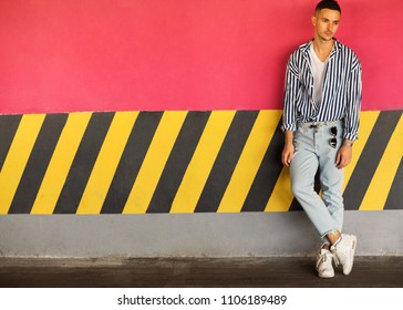 fashion guy in a striped shirt is standing near a pink parking wall