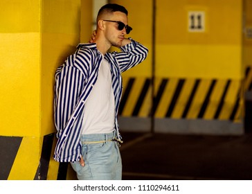 fashion guy in a striped shirt is standing near a yellow parking wall