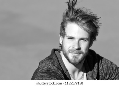 Fashion guy with stylish haircut. Bearded man with long blond hair outdoor. Macho with beard in sportswear on sunny day. Lifestyle for young man. Mens beauty at barber and hair salon, copy space.