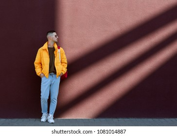 fashion guy in sunglasses and a yellow jacket posing near lilac wall