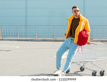 fashion guy in sunglasses and a yellow jacket jump in a cart from food in the supermarket parking