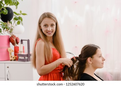 Fashion hairdresser doing hairstyle to young female client