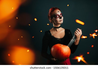 Fashion halloween model girl with skull make up pumpkin and knife explosion effect. Halloween card