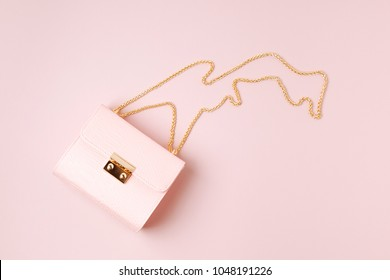 Fashion handbag on pale pink background. Flat lay, top view. Spring/summer fashion concept in pastel colored