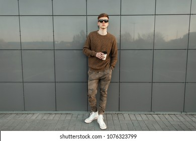 Fashion handsome hipster man with coffee in sunglasses with military pants, a sweater and white shoes standing on the street near the wall