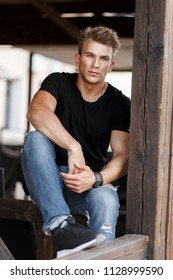 Fashion handsome young man with hair in a black shirt and jeans sitting on wooden porch